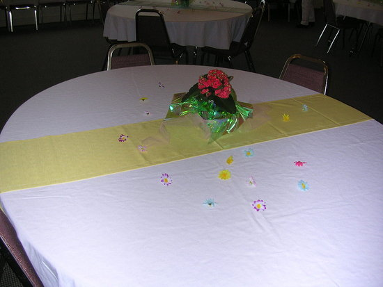 One of many beautiful tables, each with either yellow, green or blue runner, flower confetti, and a potted plant for the retiree