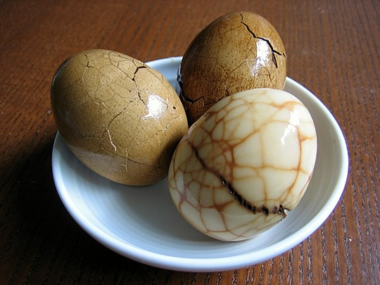 Boiled eggs cracked and steeped in a hot mixture of black tea leaves, soy sauce, and cinnamon stick.